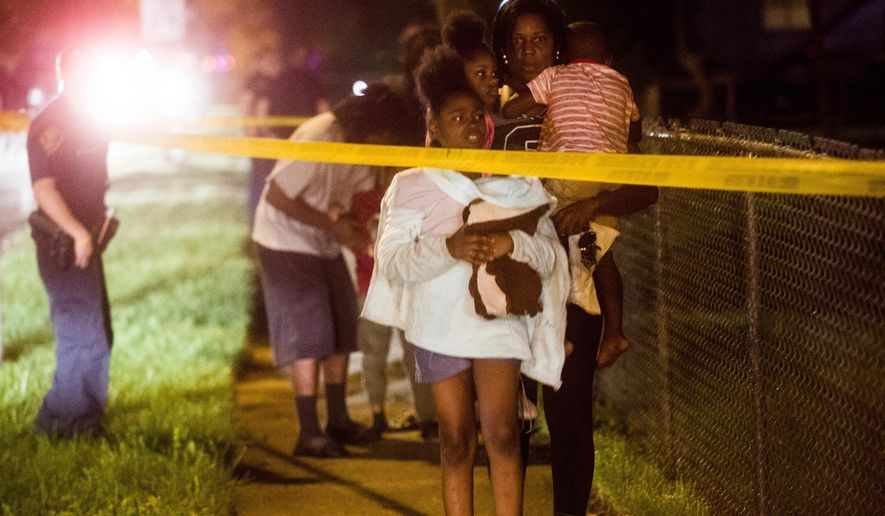 Family members leave the scene as Flint police investigate after a 7-year-old girl was shot and killed on Tuesday, Oct. 9, 2018, on the north side of Flint, Mich. No suspect information was immediately available. (Jake May/The Flint Journal via AP)