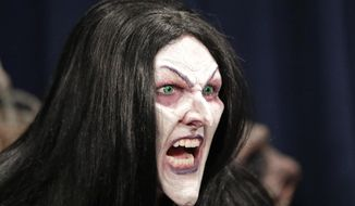 In this Wednesday, Sept. 12, 2018 photo, Laura Law gets into character after her makeup nears completion as a witch for Halloween Horror nights at Universal Studios in Orlando, Fla. (AP Photo/John Raoux)