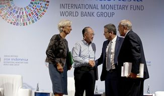 World Bank President Jim Yong Kim, second left, greets Director General of the World Trade Organization Roberto Azevedo, second right, Managing Director of International Monetary Fund (IMF) Christine Lagarde, left, and Secretary General of the Organization for Economic Co-operation and Development Angel Gurria during a trade conference in Bali, Indonesia Wednesday, Oct. 10, 2018. (AP Photo/Firdia Lisnawati)