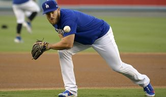 Los Angeles Dodgers' Max Muncy fields a ball during practice for Game 1 of the baseball team's NLCS against the Milwaukee Brewers, Wednesday, Oct. 10, 2018, in Los Angeles. With all the high-priced talent on the Dodgers' roster, Muncy had to find a way to stand out. He's done it with his bat, coming from the minors to lead the team in home runs. (AP Photo/Mark J. Terrill)