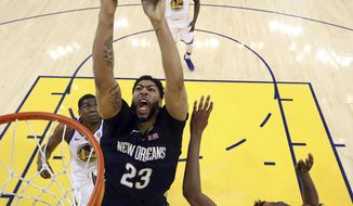 FILE - In this May 8, 2018, file photo, New Orleans Pelicans' Anthony Davis, center, goes up for a shot as Golden State Warriors' Kevon Looney, bottom left, and Kevin Durant defend during the first half in Game 5 of an NBA basketball second-round playoff series, in Oakland, Calif. The Pelicans have moved on from DeMarcus Cousins and Rajon Rondo. They've gotten younger, intend to play faster and hope that helps All-Star Anthony Davis carry the team even farther than last year's second-round playoff exit. (Ezra Shaw/Pool Photo via AP, File)