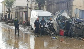 Police officers stand next to vehicles destroyed in Sant Llorenc, the town hardest hit by the downpours located 60 kilometers (40 miles) east of Mallorca's capital, Palma, Spain, on Wednesday, Oct. 10, 2018. At least five people died and five more remained missing on Wednesday after torrential rainstorms caused flash flooding in Spain's Mallorca island, authorities said. (AP Photo/Juan Pedro Martinez)