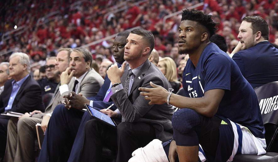 FILE - In this April 25, 2018, file photo, Minnesota Timberwolves guard Jimmy Butler, right, watches from the bench during the second half in Game 5 of the team's first-round NBA basketball playoff series against the Houston Rockets, in Houston. With Butler's status still unresolved, coach Tom Thibodeau and the Timberwolves head toward the season coming off the franchise's first playoff appearance in 14 years but carrying yet a still-cloudy outlook despite the super-max contract Karl-Anthony Towns.(AP Photo/Eric Christian Smith, File) **FILE**