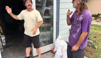 Dwight Williams, left, and Timothy Thomas discuss whether to evacuate their neighborhood in Panama City Beach, Fla., on Tuesday, Oct. 9, 2018. Thomas figures he and his wife will be safe from rising ocean water since they live in a second-story apartment. Others also aren't leaving, and a bar along the beachfront road threw a hurricane party less than 2 miles away from Thomas' home as Michael pushed toward shore Tuesday night. (AP Photo/Jay Reeves)