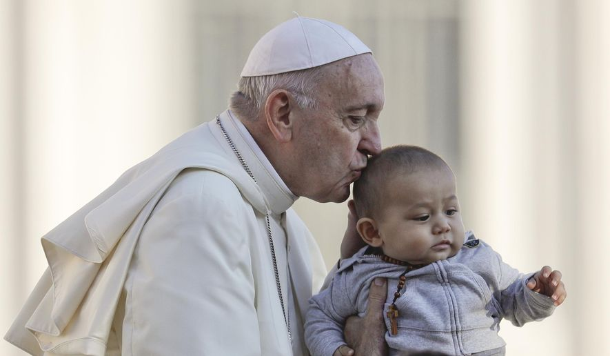 Pope Francis kisses a child as he arrives with the popemobile in St. Peter's Square to held his weekly general audience at the Vatican, Wednesday, Oct. 10, 2018. (AP Photo/Gregorio Borgia)
