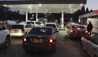 Motorists wait to fill up their tanks at a fuel station in Harare, Tuesday, Oct, 9, 2018. As Zimbabwe plunges into its worst economic crisis in a decade, gas lines are snaking for hours, prices are spiking and residents goggle as the new government insists that the country somehow has risen to middle income status. (AP Photo/Tsvangirayi Mukwazhi)
