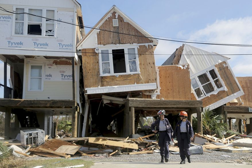 Emergency workers Dr. Patricia Cantrell, left, and Ana Kaufmann, with the South Florida Search and Rescue Task Force 2, survey damage at the western edge of town in Mexico Beach, Fla., after Hurricane Michael swept through the area Thursday, Oct. 11, 2018. (Douglas R. Clifford/Tampa Bay Times via AP)