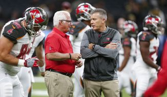 "In this Nov. 5, 2017, photo, Tampa Bay Buccaneers defensive coordinator Mike Smith, left, talks with head coach Dirk Koetter before an NFL football game against the New Orleans Saints, in New Orleans. The Bucs' defensive woes have put the heat on coordinator Mike Smith, a former head coach of the Falcons. But head coach Dirk Koetter has resisted calls to make a change. ""Every week, every game, it's way bigger than any one guy,"" Koetter said. ""It's never all one person's fault and it's never all one person's credit."" (AP Photo/Butch Dill) **FILE**"