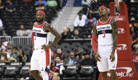Washington Wizards guard John Wall (2) and guard Bradley Beal (3) stand on the court during the first half of an NBA preseason basketball game against the New York Knicks, Monday, Oct. 1, 2018, in Washington. (AP Photo/Nick Wass) ** FILE **