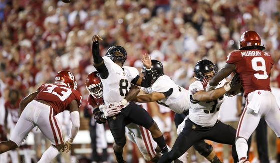 Army quarterback Kelvin Hopkins Jr. (8) gets hit by Oklahoma defensive lineman Kenneth Mann (55) while passing during an NCAA college football game in Norman, Okla., Saturday, Sept. 22, 2018. Oklahoma won 28-21 in overtime. (Ian Maule/Tulsa World via AP)