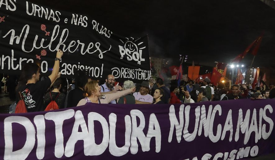 "Demonstrators carry a banner that reads in Portuguese ""Dictatorship never again,"" during a protest against Jair Bolsonaro, a far-right presidential candidate in Sao Paulo, Brazil, Wednesday, Oct. 10, 2018. Bolsonaro will face off with Workers Party candidate Fernando Haddad in an election runoff on Oct. 28. (AP Photo/Andre Penner)"