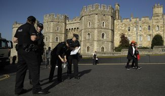A police team check and seal a drain cover outside Windsor Castle ahead of the wedding of Britain's Princess Eugenie in Windsor, England, Wednesday, Oct. 10, 2018. The 28-year-old granddaughter of Queen Elizabeth II is due to marry liquor company executive Jack Brooksbank on Friday in St. George's Chapel at Windsor Castle. (AP Photo/Matt Dunham)
