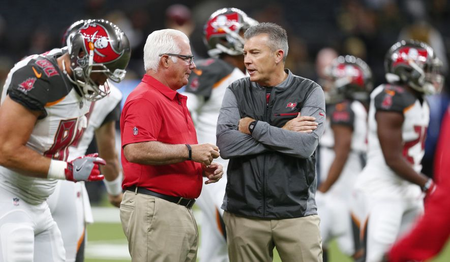 "FILE - In this Nov. 5, 2017, file photo, Tampa Bay Buccaneers defensive coordinator Mike Smith, left, talks with head coach Dirk Koetter before an NFL football game against the New Orleans Saints, in New Orleans. The Bucs' defensive woes have put the heat on coordinator Mike Smith, a former head coach of the Falcons. But head coach Dirk Koetter has resisted calls to make a change. ""Every week, every game, it's way bigger than any one guy,"" Koetter said. ""It's never all one person's fault and it's never all one person's credit."" (AP Photo/Butch Dill, File)"