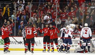 New Jersey Devils' Kyle Palmieri, center, celebrates his goal with teammates during the first period of an NHL hockey game against the Washington Capitals on Thursday, Oct. 11, 2018, in Newark, N.J. (AP Photo/Adam Hunger)