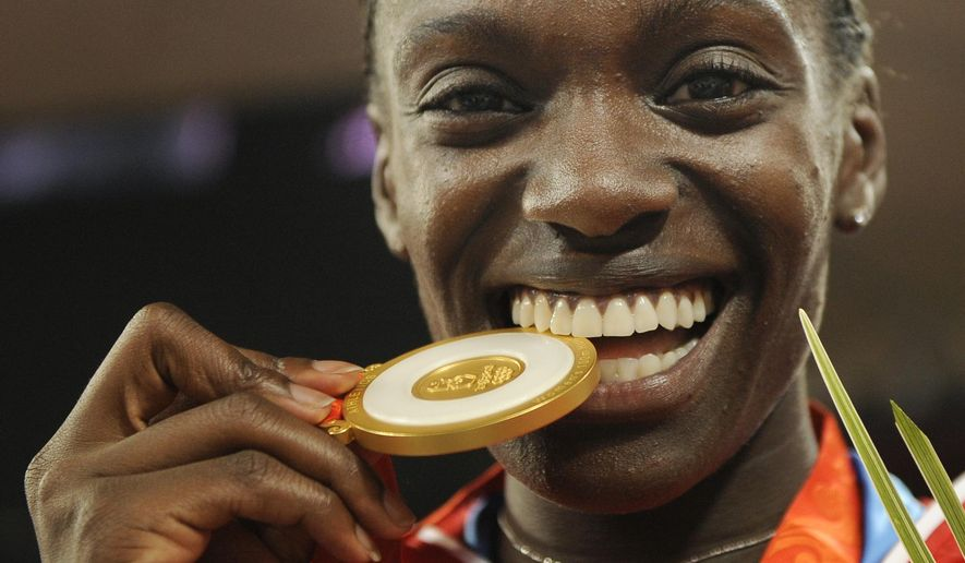 FILE - In this Aug. 19, 2008 file photo, U.S. Olympian Dawn Harper-Nelson bites her gold medal during an awarding cermeony for the women's 100-meter hurdles winners at the Beijing 2008 Olympics in Beijing. More than 20 years after going over her first hurdle, Harper-Nelson has decided to pursue other dreams. Citing a desire to start her family, the 2002 graduate of East St. Louis Senior High School has announced her retirement from track and field competition. (AP Photo/Mark J. Terrill File)