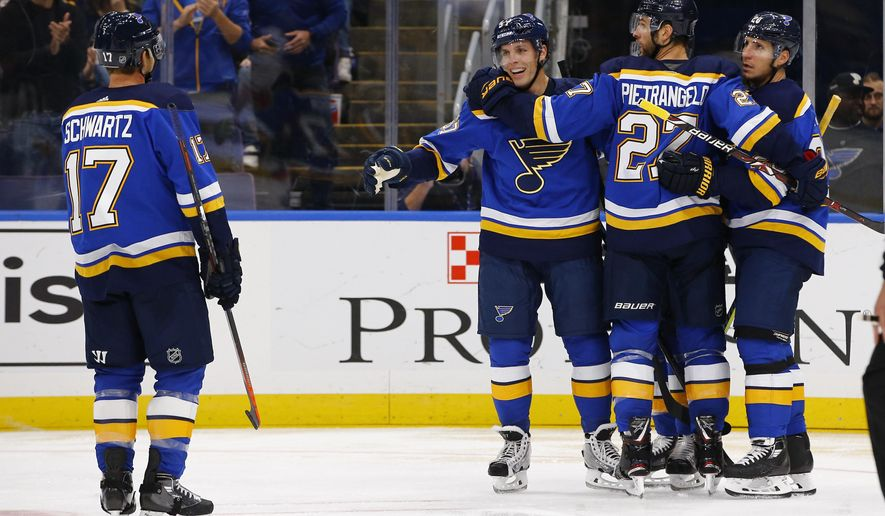 St. Louis Blues' David Perron (57) is congratulated by Jaden Schwartz (17), Alex Pietrangelo (27), and Alexander Steen (20) after scoring a goal during the second period of an NHL hockey game against the Calgary Flames on Thursday, Oct. 11, 2018, in St. Louis. (AP Photo/Billy Hurst)
