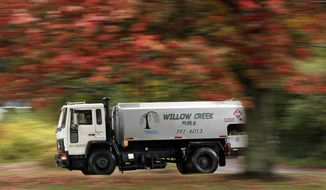 A heating oil delivery truck travels down a road in South Portland, Maine, Thursday, Oct. 11, 2018. With winter on its way, heating oil keeps growing more costly as several top oil-producing countries remain in political or economic turmoil. The Governor's Energy Office says the average statewide cash price is now $2.96, 78 cents per gallon higher than a year ago. (AP Photo/Robert F. Bukaty)