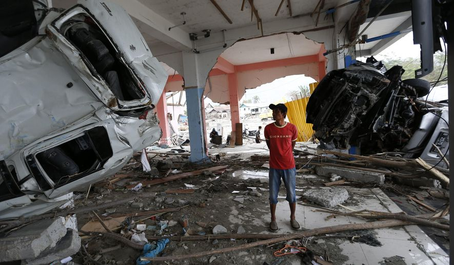 A man inspects the wreckage of vehicles inside a building at the tsunami-ravaged area in Palu, Central Sulawesi, Indonesia, Thursday, Oct. 11, 2018. A 7.5 magnitude earthquake rocked Central Sulawesi province on Sept. 28, triggering a tsunami and mudslides that killed a large number of people and displaced tens of thousands of others. (AP Photo/Dita Alangkara)