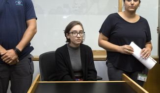 American Lara Alqasem, center, sits in a courtroom prior to a hearing at the district court in Tel Aviv, Israel, Thursday, Oct. 11, 2018. A senior Israeli cabinet minister on Wednesday defended the government's handling of the case of an American graduate student held in detention at the country's international airport for the past week over allegations that she promotes a boycott against the Jewish state. (AP Photo/Sebastian Scheiner)