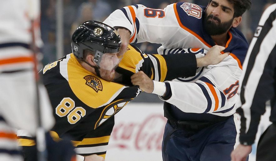 Boston Bruins defenseman Kevan Miller (86) and Edmonton Oilers left wing Jujhar Khaira (16) fight during the second period of an NHL hockey game Thursday, Oct. 11, 2018, in Boston. (AP Photo/Mary Schwalm)