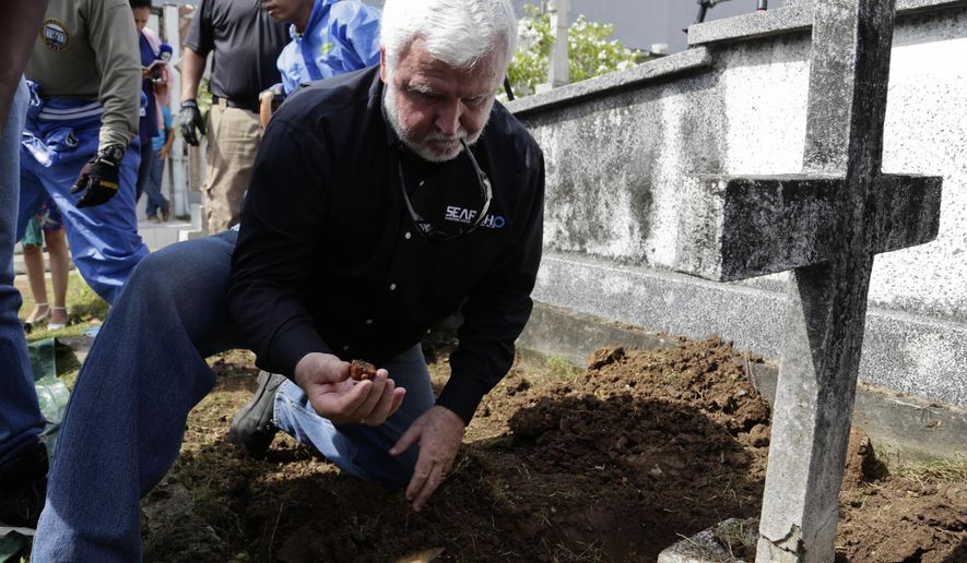 Maritime archaeologist James Delgado inspects debris on the grave site of Julius H. Kroehl before exhuming his body from Amador Cemetery in the Chorrillo neighborhood of Panama City, Thursday, Oct. 11, 2018. The remains of Kroehl, a German-American who was a pioneer on the design of the first submarine to submerge successfully at depth, are being moved to Corozal Cemetery, a cemetery where American veterans are buried. (AP Photo/Arnulfo Franco)
