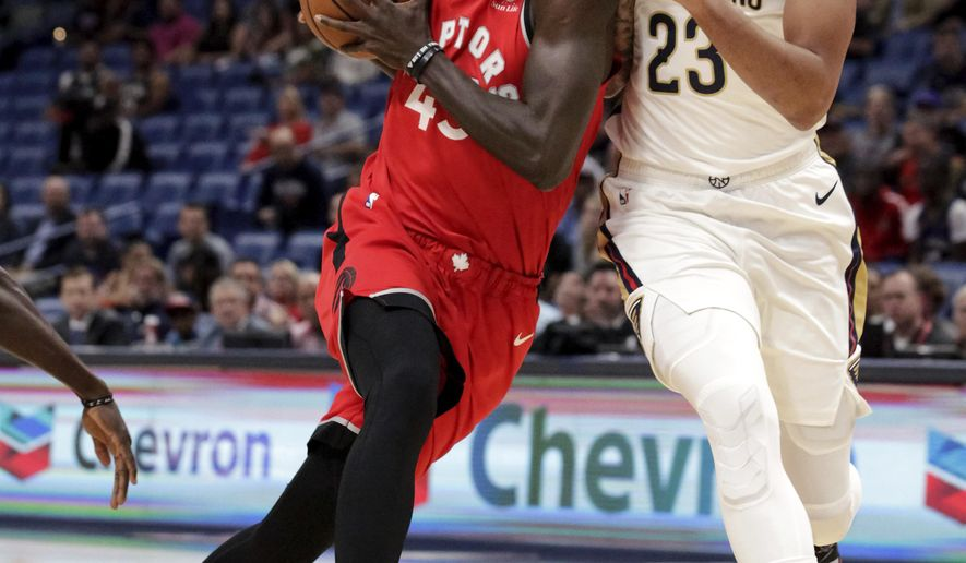 Toronto Raptors forward Pascal Siakam (43) drives against New Orleans Pelicans forward Anthony Davis (23) during the first half of a preseason NBA basketball game in New Orleans, Thursday, Oct. 11, 2018. (AP Photo/Scott Threlkeld)
