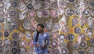 A woman attends the opening of an exhibition of South African abstract artist Christo Coetzee, who died in 2000 and is largely unknown in his home country, on Thursday, Oct. 4, 2018. The retrospective show at the Standard Bank Gallery in Johannesburg aims to stoke interest in Coetzee, who won some international acclaim decades ago. (AP Photo/Christopher Torchia)