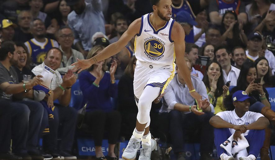 Golden State Warriors' Stephen Curry celebrates after scoring against the Phoenix Suns during the first half of a preseason NBA basketball game Monday, Oct. 8, 2018, in Oakland, Calif. (AP Photo/Ben Margot)