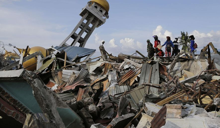 In this Oct. 6, 2018, photo, villagers wait for any word on their missing relatives lost in the Balarola neighborhood of Palu city when a massive earthquake caused the soil to loosen like a liquid, swallowing some homes whole and collapsing others into piles of rubble in Central Sulawesi, Indonesia. The 7.5 magnitude quake triggered not just a tsunami that leveled huge swathes of the region's coast, but a geological phenomenon known as liquefaction, making the soil move like liquid and swallowing entire neighborhoods. (AP Photo/Aaron Favila, File)