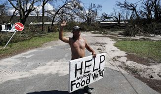 "Michael Williams, 70, waves to passing motorists while looking for food and water as downed trees prevent him from driving out of his damaged home with his family in the aftermath of Hurricane Michael in Springfield, Fla., Thursday, Oct. 11, 2018. ""I don't know what I'm going to,"" said Williams. (AP Photo/David Goldman)"