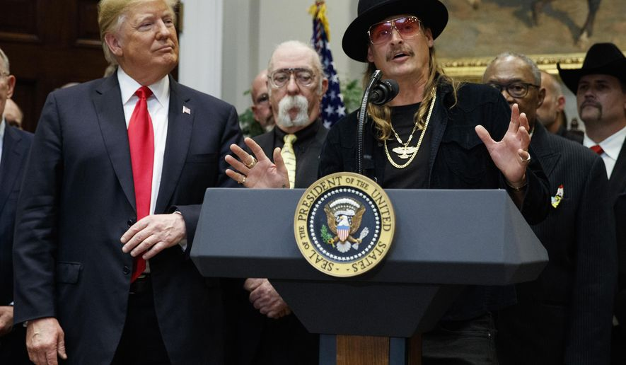 """President Donald Trump looks on as musician Kid Rock speaks during a signing ceremony for the """"Orrin G. Hatch-Bob Goodlatte Music Modernization Act,"""" in the Oval Office of the White House, Thursday, Oct. 11, 2018, in Washington. (AP Photo/Evan Vucci)"""