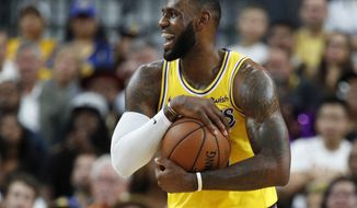 Los Angeles Lakers forward LeBron James reacts after a play against the Golden State Warriors during the first half of an NBA preseason basketball game Wednesday, Oct. 10, 2018, in Las Vegas. (AP Photo/John Locher)