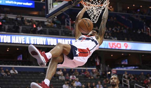 Washington Wizards forward Devin Robinson (7) dunks over Guangzhou Long-Lions guard Kyle Fogg during the second half of an NBA preseason basketball game Friday, Oct. 12, 2018, in Washington. (AP Photo/Nick Wass) ** FILE **