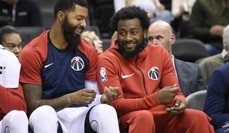 Washington Wizards guard John Wall, right, smiles next to Markieff Morris on the bench during the first half of the team's NBA exhibition basketball game against the Guangzhou Long-Lions, Friday, Oct. 12, 2018, in Washington. (AP Photo/Nick Wass) ** FILE **