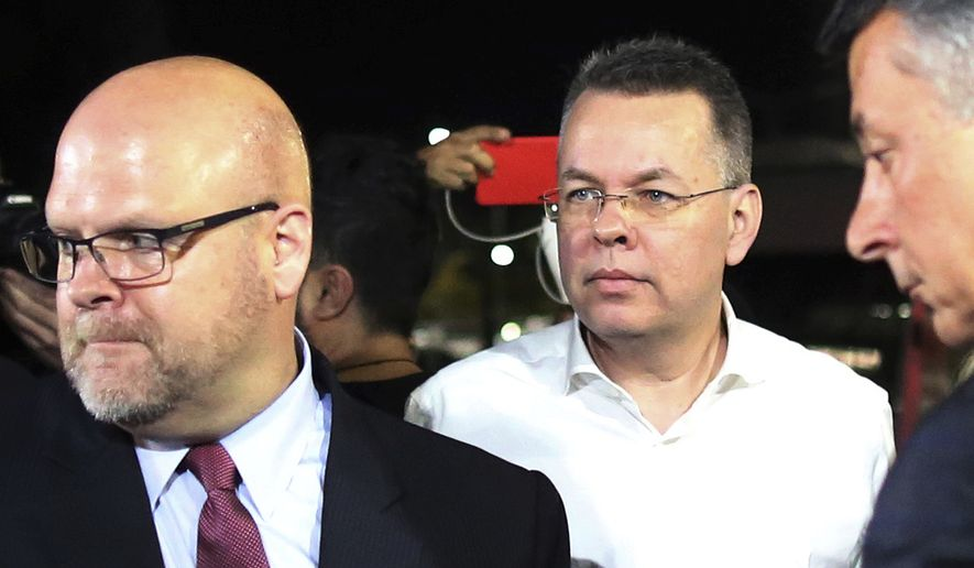 Pastor Andrew Brunson, center, and U.S. Charge d'Affaires Jeffrey Hovenier, left, arrive at Adnan Menderes airport for a flight to Germany after his release following his trial in Izmir, Turkey, Friday, Oct. 12, 2018, A Turkish court on Friday convicted an American pastor of terror charges but released him from house arrest and allowed him to leave Turkey, in a move that is likely to ease tensions between Turkey and the United. (AP Photo/Emre Tazegul)