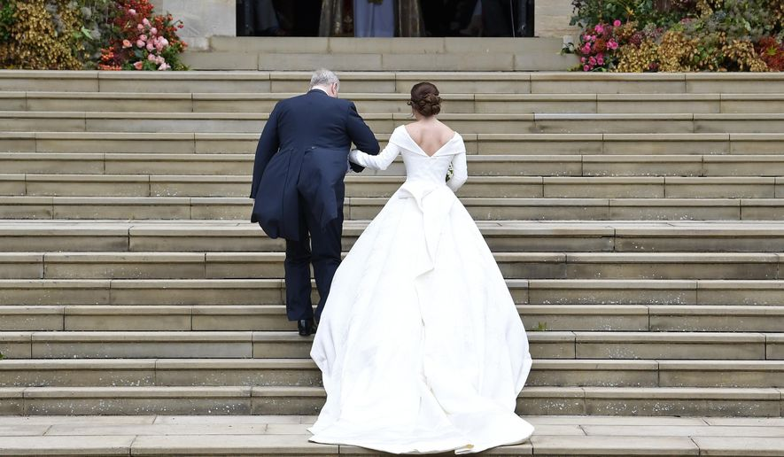 Britain's Princess Eugenie, accompanied by her father Prince Andrew, arrives for her wedding ceremony to Jack Brooksbank in St George's Chapel, Windsor Castle, near London, England, Friday Oct. 12, 2018. (Toby Melville, Pool via AP)