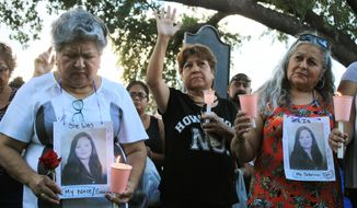 FILE - In this  Sept. 18, 2018, file photo, dozens of family members and friends of four women who authorities say were killed by a U.S. Border Patrol agent Juan David Ortiz, gather for a candlelight vigil at a park in downtown Laredo, Texas.  The Border Patrol sector in Laredo, Texas,  where two agents were accused this year of multiple murders in separate cases, disciplined employees more over two years than any other major sector, according to data released by U.S. Customs and Border Protection Friday. (AP Photo/Susan Montoya Bryan, File)