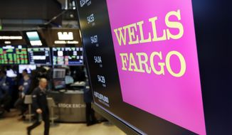 FILE- In this May 17, 2018, file photo the logo for Wells Fargo appears above a trading post on the floor of the New York Stock Exchange. Wells Fargo reports earnings Friday, Oct. 12, 2018. (AP Photo/Richard Drew, File)