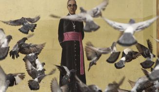 In this Oct. 3. 2018 photo, pigeons fly in front of a mural of Archbishop Oscar Arnulfo Romero, located on a wall of the Metropolitan Cathedral in San Salvador, El Salvador. Romero who was killed in 1980 by a right wing will death squad during mass, will be canonized in Rome by Pope Francis on Sunday, Oct. 14, 2018. (AP Photo/Salvador Melendez)