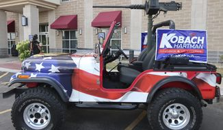 FILE - In this Aug. 7, 2018 file photo, a jeep with a replica machine gun mounted on back sits outside the hotel where Kansas Secretary of State Kris Kobach's supporters were meeting in Topeka, Kan. Organizers of a small-town Kansas parade have told Kobach that he must remove the replica machine gun from the vehicle that's become a key part of his campaign for governor and emblematic of his no-apologies style. An attorney for the organizing committee for Iola's Farm City Days said it was in talks Friday Oct. 12, 2018, with Kobach's campaign to find a compromise. (AP Photo/John Hanna File)
