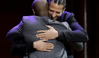 Former NFL quarterback Colin Kaepernick, right, hugs comedian Dave Chappelle, left, on stage during W.E.B. Du Bois Medal award ceremonies, Thursday, Oct. 11, 2018, at Harvard University, in Cambridge, Mass. Kaepernick and Chappelle are among eight recipients of Harvard University's W.E.B. Du Bois Medals in 2018. Harvard has awarded the medal since 2000 to people whose work has contributed to African and African-American culture. (AP Photo/Steven Senne)