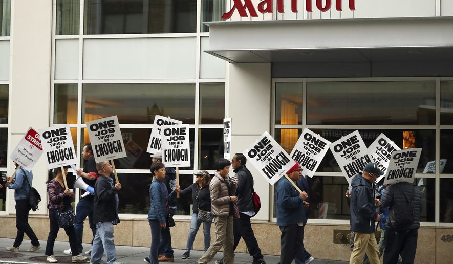 FILE - In this Oct. 4, 2018 file photo, hotel workers strike in front of a Marriott hotel in San Francisco. New technology threatening to make some hotel jobs obsolete is among the concerns prompting thousands of Marriott workers to walk off their jobs across the U.S. in recent weeks. (AP Photo/Ben Margot, File)