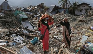Indonesian women stand on the rubble as they look for what's left from a relative's house at Balaroa neighborhood in Palu, Central Sulawesi, Indonesia, Thursday, Oct. 11, 2018. Indonesia's search for victims buried in neighborhoods annihilated by an earthquake and tsunami is nearing its end almost two weeks after the double disasters hit the remote city. (AP Photo/Dita Alangkara)