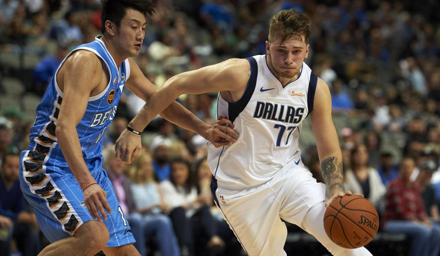 FILE - In this Saturday, Sept. 29, 2018, file photo, Dallas Mavericks guard Luka Doncic (77) drives to the basket against Beijing Ducks forward Duan Jiangpeng (11) during the second half of an NBA exhibition basketball game in Dallas. Doncic has help from plenty of angles as a teenager transitioning from European ball to the NBA with the Mavericks. (AP Photo/Cooper Neill, File)