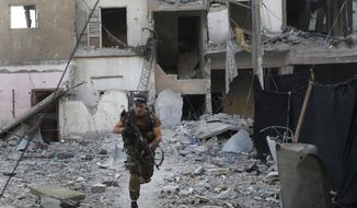 FILE - In this Thursday, July 27, 2017, a U.S.-backed Syrian Democratic Forces fighter runs in front of a damaged building as he crosses a street on the front line, in Raqqa city, Syria. With Islamic State's near total defeat on the battle field, the extremist group has reverted to what it was before its spectacular series of conquests in 2014 _ a shadowy terror network that targets vulnerable civilian populations and exploits state weaknesses to incite on sectarian strife. But a recent surge in false claims of responsibility for attacks also signals that the group is struggling to stay relevant after losing its proto-state and its dominance of the international news agenda. (AP Photo/Hussein Malla, File)