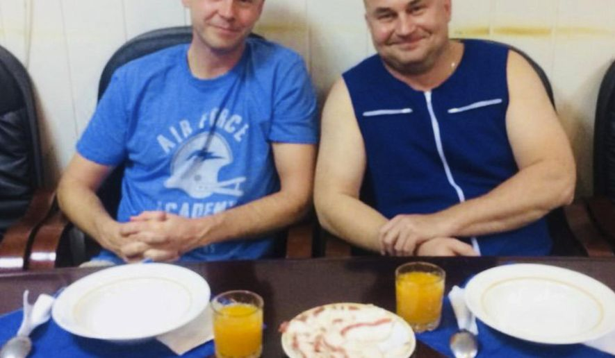 In this photo released by Roscosmos, NASA Astronaut Nick Hague, left, and Roscosmos cosmonaut Alexei Ovchinin pose for a photo in Baikonur, Kazakhstan on Thursday, Oct. 11, 2018, after an emergency landing following the failure of a Russian booster rocket carrying them to the International Space Station. (Roscosmos via AP)
