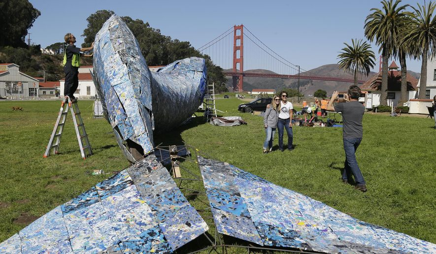 Artist Joel Deal Stockdill, left, works on a blue whale art piece made from discarded single-use plastic at Crissy Field Friday, Oct. 12, 2018, in San Francisco. Artists are putting the finishing touches on an 82-foot-long (24-meter-long) blue whale made from discarded plastic that will be in display near San Francisco's Golden Gate Bridge to raise awareness about ocean pollution. The Monterey Bay Aquarium said Friday a blue whale can weigh about 300,000 pounds, about the amount of plastic that ends up in the ocean every nine minutes. (AP Photo/Eric Risberg)
