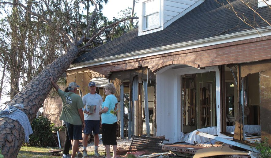 Rex Buzzett, far left, his son Josh Buzzett and neighbor Hilda Duren stand outside the Buzzett's home, Thursday, Oct. 11, 2018, that was gutted by a storm surge in Port St. Joe, Fla. Hurricane Michael devastated several homes overlooking the Gulf of Mexico in Port St. Joe, while largely sparing residents of the neighboring Gulf community of Apalachicola. (AP Photo/Russ Bynum)