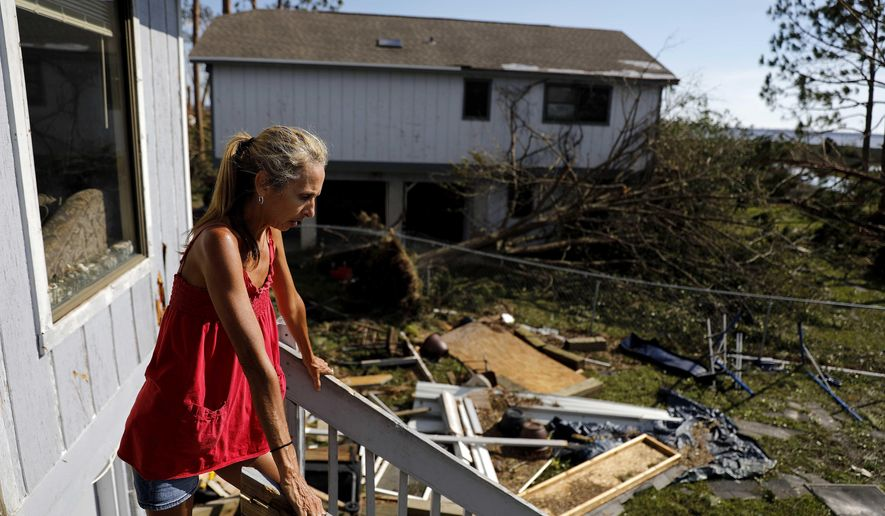 "Monica Jones looks out over the debris littering her yard after riding out hurricane Michael in her home in Callaway, Fla., Thursday, Oct. 11, 2018. ""I didn't think it was going to be this bad,"" said Jones on her decision to stay through the storm. The devastation inflicted by Hurricane Michael came into focus Thursday with rows upon rows of homes found smashed to pieces, and rescue crews began making their way into the stricken areas in hopes of accounting for hundreds of people who may have stayed behind. (AP Photo/David Goldman)"