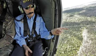 Florida Gov. Rick Scott points out some damage caused by Hurricane Michael while flying somewhere over the panhandle of Florida Thursday, Oct. 11, 2018. The devastation inflicted by Hurricane Michael came into focus Thursday with rows upon rows of homes found smashed to pieces, and rescue crews began making their way into the stricken areas in hopes of accounting for hundreds of people who may have stayed behind. (AP Photo/Chris O'Meara)